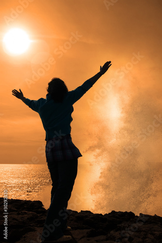 silhouette of lone woman facing a powerful wave in sunshine