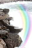 wave crashing on coast cliffs with rainbow