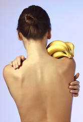 Young woman standing and keeps a bananas on her shoulder