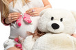 A woman holds her baby pink toe pregnant belly and soft toy bear