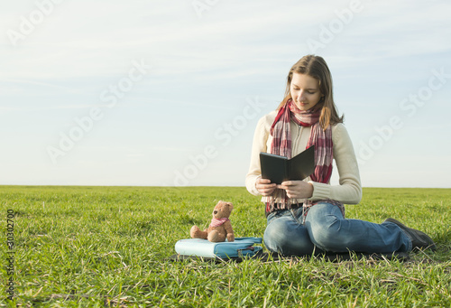 Girl reading a ebook sitting at grass