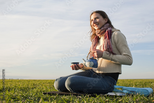 Girl with teapot sitting at grass