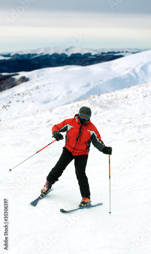 Skier man in snow-covered mountains
