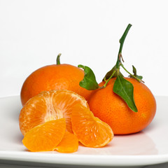 Sweet, juicy Clementines on white plate.