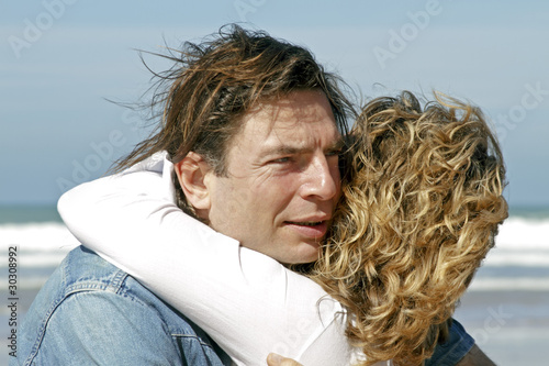 Young couple in love hugging eachother at the beach