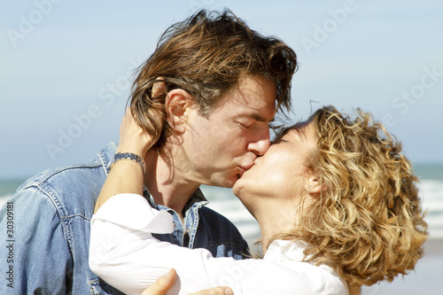 Young couple in love kissing eachother at the beach
