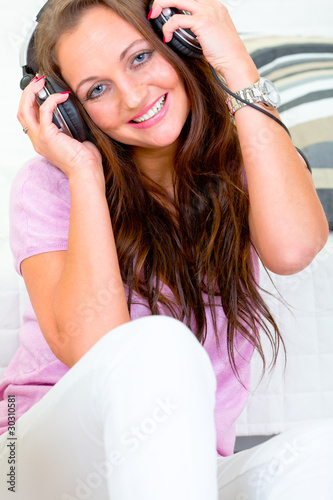 Smiling woman relaxing and listening music in headphones.
