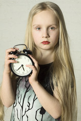 Beautiful girl holding alarm clock