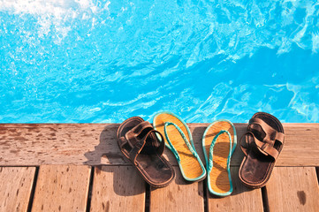 Two pairs (men's and woman's) of flip-flops by swimming pool