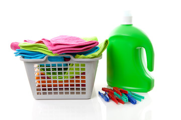 Laundry basket filled with colorful folded towels, pegs and bott