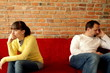 Relationship difficulties, young couple sitting on sofa apart