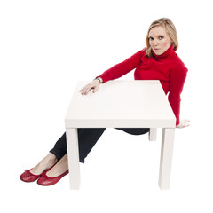 Young woman sitting at funny small desk
