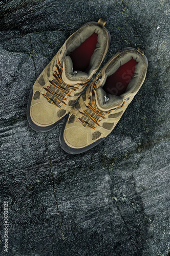 Walking boots on rock background