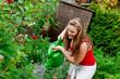 Frau im Garten beim Gießen der Blumen