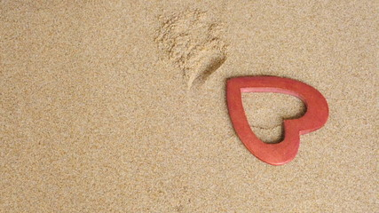 a wooden heart dropping on the sand