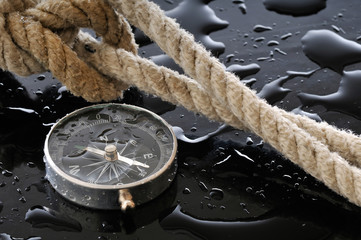 Wet compass and knot on black background