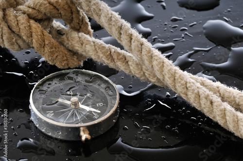 Leinwandbild Motiv Wet compass and knot on black background