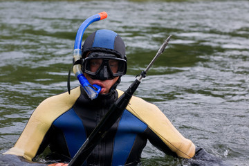 Diver with a gun for underwater hunting in a water
