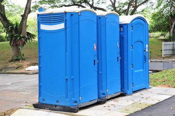 A Row Of Three Blue Color Portable Toilets