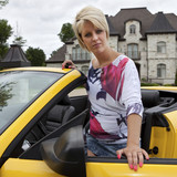 Wealthy young woman getting into a convertible car poster