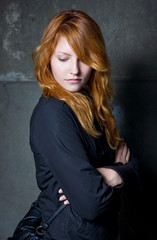 Moody portrait of a beautiful fashoinable young redhead girl