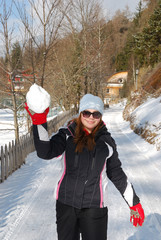 Girl with red gloves throwing a snowball
