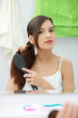 Beautiful young woman brushing her hair
