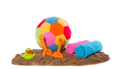 cheerful beach toys and towels in the sand isolated over white