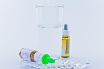 Wasserglas mit Medikamenten