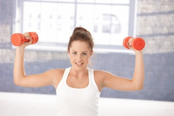 Attractive female exercising with dumbbells