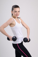 girl practicing bodybuilding with dumbbell
