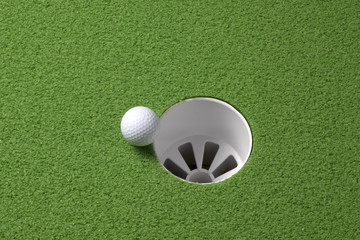 Golf ball rolls to hole