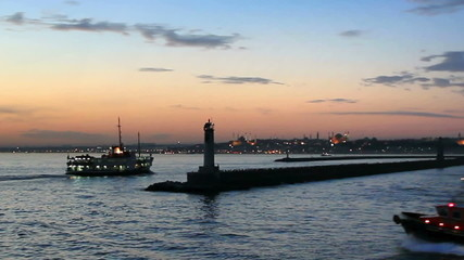 Ferry and tug boat leaves from Kadikoy harbor in sundown
