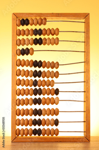wooden abacus  on a yellow background