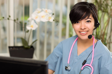 Attractive Multi-ethnic Woman Wearing Headset, Scrubs and Stetho