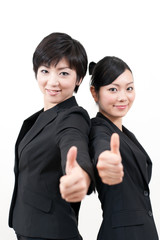 a portrait of two businesswomen showing thumb up