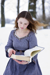 Girl in medieval dress reading the book