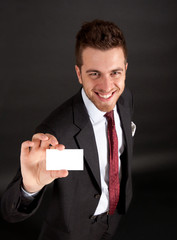 Businessman showing a businesscard, dark background
