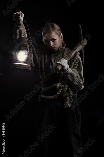 Woman holding pick and oil lamp