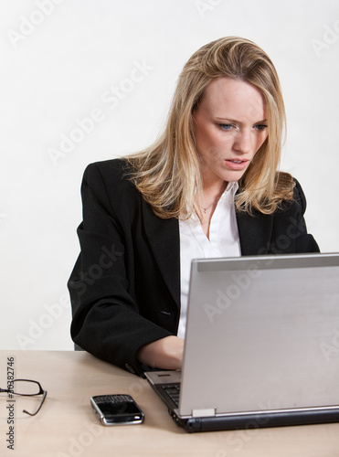 Beautiful caucasian businesswoman working on laptop