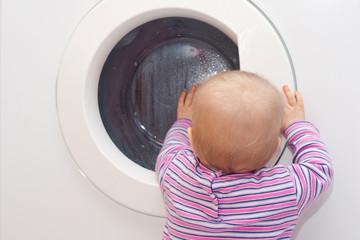 Baby schaut in die Wäschetrommel