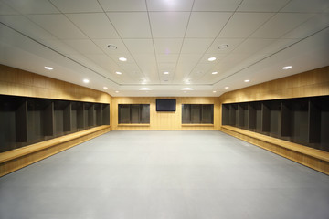 large clean locker room. gray floor and ceiling, big televisor
