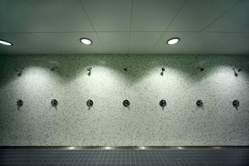 big, light, empty public shower room, green tile on walls