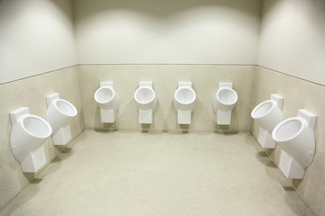 several white urinals. big, bright, clean, beautiful toilet