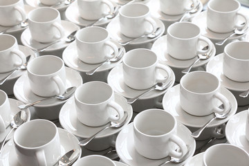 many rows of pure white cup and saucer with teaspoon