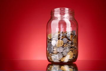 coins in money jar on red background. Ukrainian coins