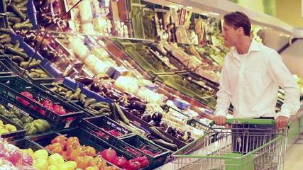Mann im Supermarkt kauft Gemüse