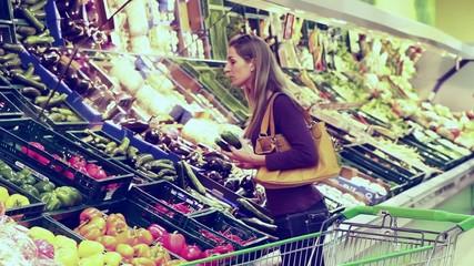 Frau im Supermarkt kauft Gemüse