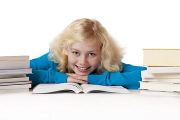 Schülerin liegt fröhlich am Boden und lernt für die Schule