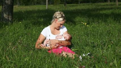 Mutter wiegt Baby auf Wiese